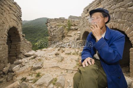 senior mann rauchen an einer wand