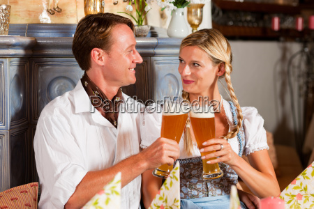 couple in tracht drinking wheat beer