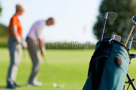 mature couple playing golf focus on