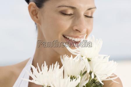 nahaufnahme einer jungen frau riechen blumen