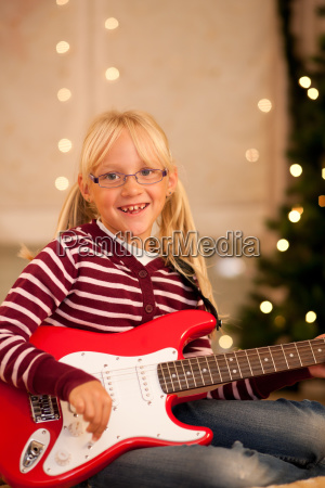 child with guitar at christmas