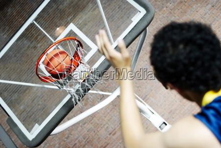 rueckansicht eines mannes basketball spielen