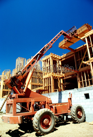 tractor lifts lumber on construction site