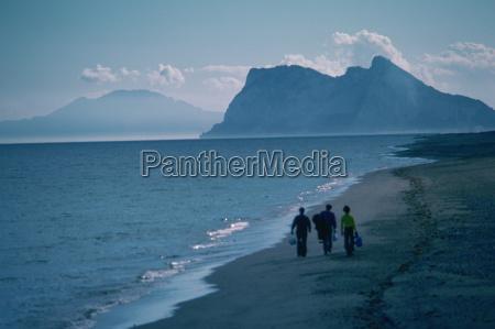 drei personen die am strand spazieren