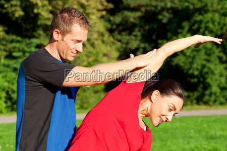 frau dehnt sich mit personal trainer