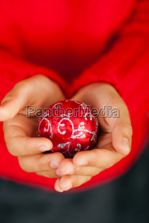 child holds christmas ball