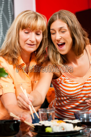 mother and daughter eating sushi