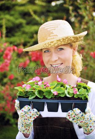 frau mit container angebauten pflanzen