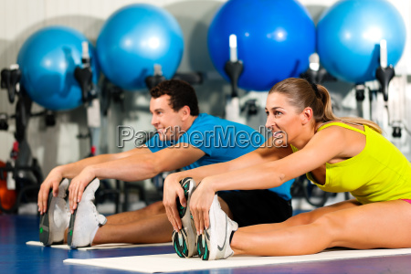 paar im fitnessstudio beim dehnen
