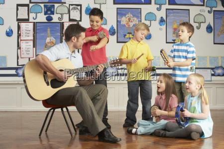 maennlicher lehrer der gitarre mit den