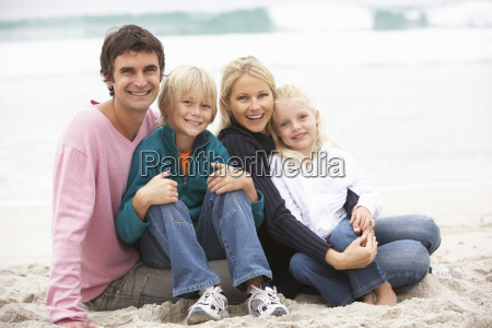 young family sitting on winter beach