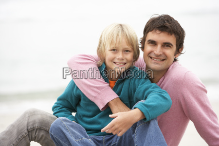 father and son sitting on winter