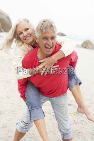 senior man giving woman piggyback on