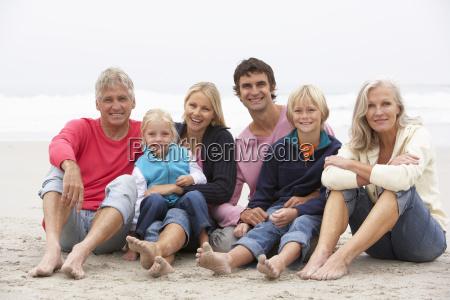 three generation family sitting on winter