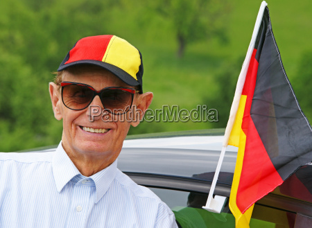senior soccer fan on car
