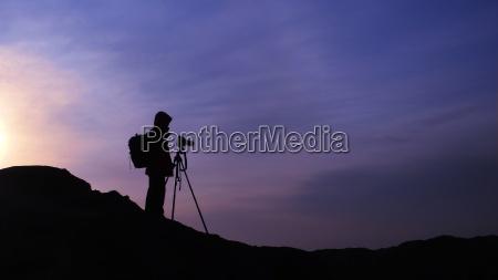 silhouette eines fotografen bei sonnenaufgang