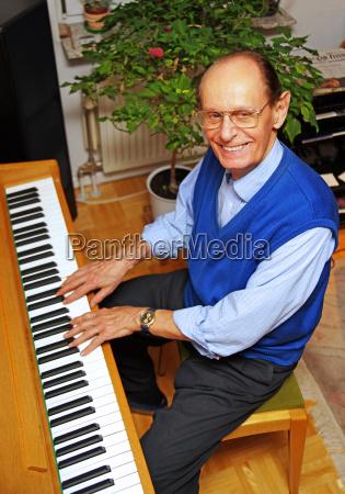 senior beim klavier spielen
