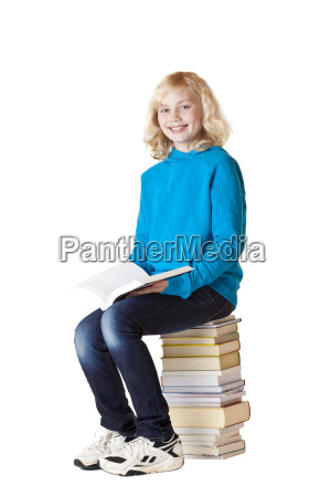 schoolgirl sitting on school books and