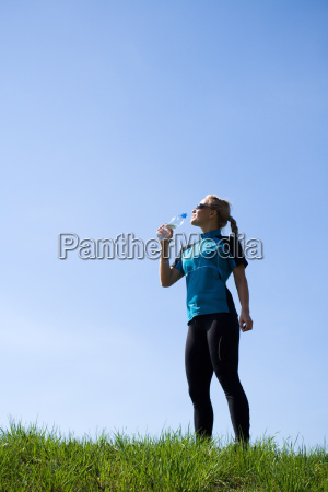 young woman drinking water during running
