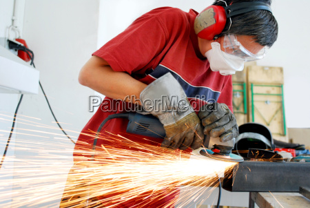 metal worker with a grinder and