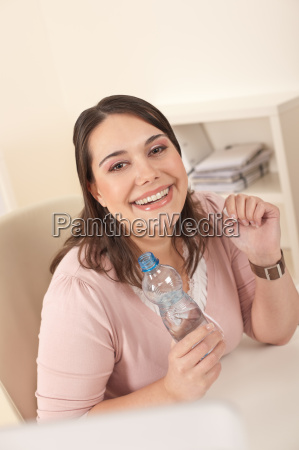 young executive woman with bottle of
