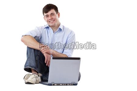 junger gut aussehender mann sitzt laessig