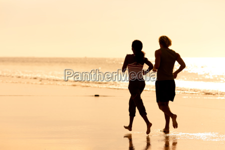 sports couple jogging on the beach