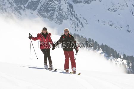 paar faehrt hand in hand ski