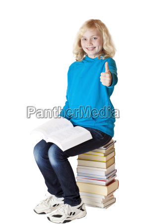 young schoolgirl on books stack shows