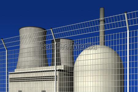 atomkraftwerk hinter einem sperrzaun vor blauem