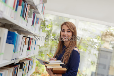 girl choosing book in library and