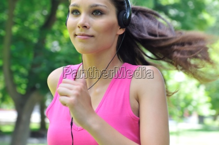 young woman with headphones running in