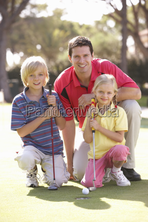 father teaching children to play golf