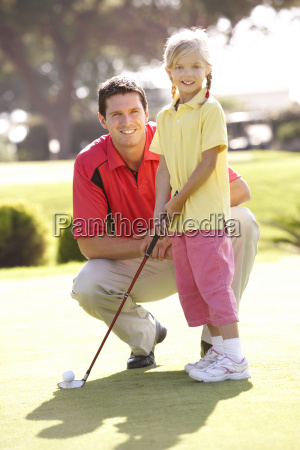 father teaching daughter to play golf