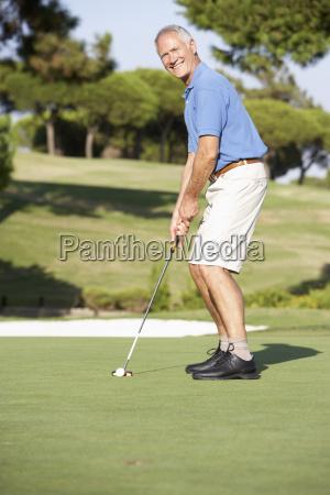aelterer maennlicher golfspieler auf golfplatz putting