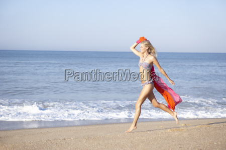 young woman running on beach