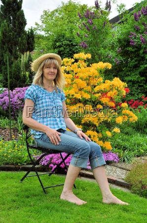blonde woman sitting in the garden