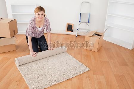 attraktive frau rollt einen teppich auf