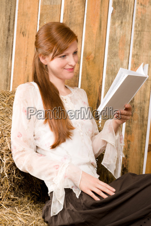 young romantic woman in barn reading