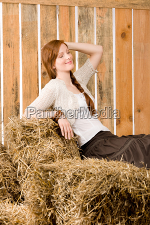 romantic young woman sitting on hay