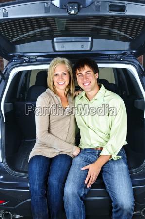 ehepaar sitzt im ruecken des autos
