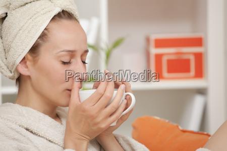 woman in bathrobe drinking tea