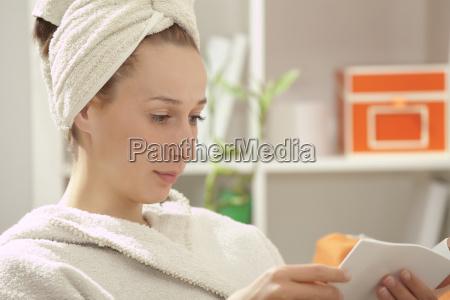 woman in bathrobe reading book