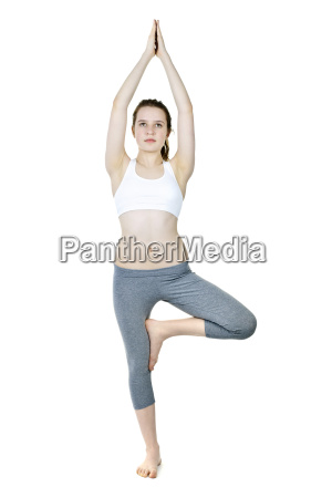 fit girl doing tree yoga pose