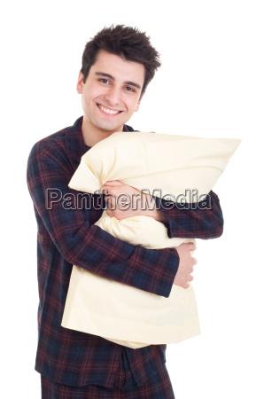 mann im pyjama holdingkissen
