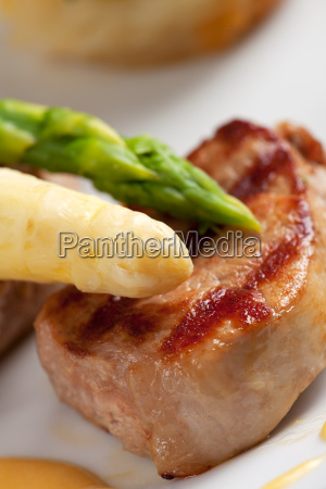 white and green asparagus on pork