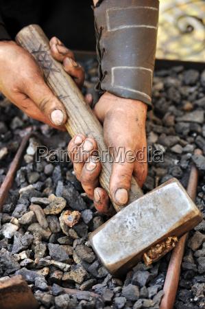 detail der schmutzigen haende halten hammer
