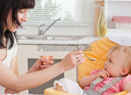beautiful brunette woman feeding her baby