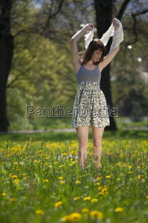 junge frau schlendert durch die fruehlingswiese