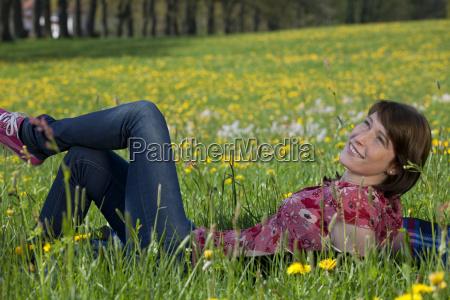 junge frau entspannt auf fruehlingswiese
